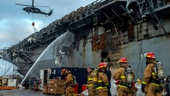 Sailors prepare to board the amphibious assault ship USS Bonhomme Richard (LHD 6) to fight an ongoing fire at Naval Base in San…