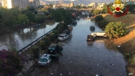 Cars are piled as others remain trapped in water and mud after an underpass, seen in the background, flooded on Wednesday in the Sicilian city of Palermo, southern Italy, as seen early on July 16, 2020.