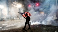 A Black Lives Matter protester carries an American flag as teargas fills the air on July 21, 2020, in Portland, Oregon.