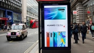 FILE - Pedestrians walk past a Huawei ad at a bus stop in central London, Britain, April 29, 2019.