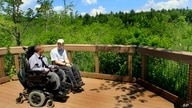 FILE - Two men in wheeelchairs enjoy the view at an overlook at Crotched Mountain Rehabilitation Center in Greenfield, New Hampshire, June 16 2011. The center offers trails designed to be easily accessible for people in wheelchairs.
