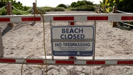 A sign is posted at a closed entrance to the beach during a spike in coronavirus cases, in the South Beach neighborhood of Miami Beach, Florida, July 3, 2020.