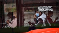 FILE - Passengers wearing face masks are seen on a bus in Bilbao, northern Spain, June 12, 2020. A county in Spain's northwestern region of Galicia has been placed on lockdown after several bars in the area reported new cases of the coronavirus.