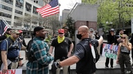 Members of a group wearing shirts with the logo of the far-right Proud Boys group argue with counter protesters during a small protest against Washington state's stay-at-home orders, Friday, May 1, 2020, in downtown Seattle.
