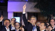 Andrej Plenkovic, Croatia's incumbent prime minister, center, waves a Croatian flag as he celebrates with his HDZ party members, in Zagreb, Croatia, July 5, 2020.
