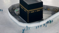 FILE - Workers disinfect the grounds around the Kaaba, a cubic building at the Grand Mosque in the Muslim holy city of Mecca, Saudi Arabia, March 7, 2020.