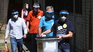 Members of a special election team with a ballot box and voting material leave municipal election commission headquarters on their way to voters who have tested positive for COVID-19 or are in self-isolation, in Skopje, North Macedonia, July 13, 2020.