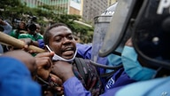 Kenyan policemen grab a protester by the throat as they detain him at a demonstration in downtown Nairobi, Kenya, July 7, 2020.