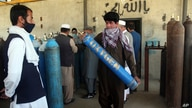 A man carries an oxygen tank from a privately owned oxygen factory in Kabul, Afghanistan, June 18, 2020. For seven years, Najibullah Seddiqi's oxygen factory sat idle. Now he refills hundreds of oxygen cylinders a day for free for COVID patients.