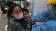 Sofia Pinto holds her son Antonio who cries out as he receives an influenza vaccine during a vaccination campaign in the Villa El Salvador neighborhood of Lima, Peru, June 26, 2020.