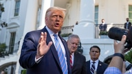 President Donald Trump, accompanied by White House Chief of Staff Mark Meadows, second from left, speaks with reporters on the South Lawn of the White House, in Washington, July 29, 2020.