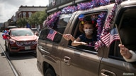 A girl is seen through the window of a car taking part in a July 4th parade amid the coronavirus pandemic, in Galveston, Texas, July 4, 2020.
