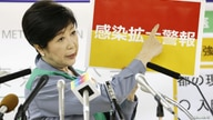 Tokyo Governor Yuriko Koike shows a banner reading 'Infection spread alert' as she attends a news conference on the latest situation reagrding the coronavirus disease (COVID-19) outbreak, in Tokyo, Japan, July 15, 2020, in this photo taken by Kyodo.