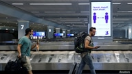 Travelers pass a sign alerting them to distance at LaGuardia Airport, during the outbreak of the coronavirus disease (COVID-19), in New York, June 29, 2020.