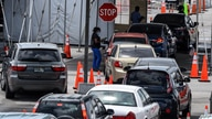 A medical staff member assists people queing in their cars at a rapid antigen coronavirus testing site at Hard Rock Stadium in…