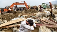 A villager reacts next to his destroyed house as rescuers search for bodies after a flash flood affected the area at Sayrah-e…