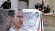 Syrians, including members of the Syrian National Defence Forces (NDF), hang a portrait of President Bashar al-Assad on June 13…