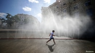 A child runs under water sprinklers during a heat wave in Vienna, Austria July 23, 2019.  REUTERS/Lisi Niesner