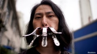 Brother Nut, Chinese performance artist with three metallic clips sealing his mouth, poses for a picture in Shanghai, following…