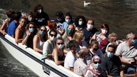 People wear protective face masks as they enjoy a boat trip on a canal in central Bruges, following the spread of the…