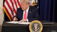 U.S. President Donald Trump signs executive orders for economic relief during a news conference amid the spread of the…