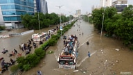People sit atop a bus roof while others wade through the flooded road during monsoon rain, as the outbreak of the coronavirus…