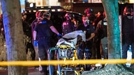 Police officers help remove the the body of a man who was shot dead amid weekend clashes in Portland, Ore.