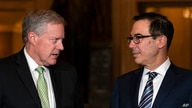Treasury Secretary Steven Mnuchin and White House chief of staff Mark Meadows look to each other as they speak to reporters.