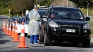 Medical staff prepare take a COVID-19 test from a visitor to a drive through community based assessment centre in Christchurch,…