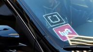 FILE - In this Jan. 12, 2016 file photo, a ride share car displays Lyft and Uber stickers on its front windshield in downtown…