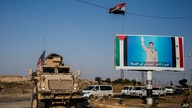 U.S. military convoy drives the he town of Qamishli, north Syria, by a poster showing Syrain President Bashar Aassad Saturday,…