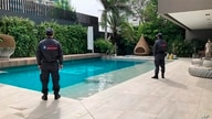 In this photo distributed by Colombia's Attorney Generals Office, officials pose with their backs to the camera by a pool on a property allegedly belonging to Alex Saab in Barranquilla, Colombia, July 22, 2020.
