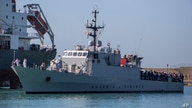 FILE - Migrants arrive in Porto Empedocle, Sicily, aboard two military ships after being transferred from the island of Lampedusa, where a number of small boat carrying migrants arrived in the last days, July 27, 2020.