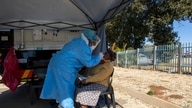 A woman has a sample collected for coronavirus testing during the screening and testing campaign aimed to combat the spread of COVID-19, in Eldorado Park outside of Johannesburg, South Africa, Aug. 3, 2020.