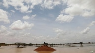 A Sudanese sits on a mound at a flooded field near the town of Osaylat, 60 km southeast of the capital in Khartoum, Sudan, Aug. 7, 2020.