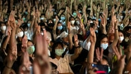 Pro-democracy students raise a three-finger salute, a resistance symbol borrowed by Thailand's anti-coup movement from the…