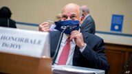 Postmaster General Louis DeJoy removes his face mask as he arrives to testify before a House Oversight and Reform Committee.