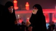 Shiite Muslim worshippers wearing protective face masks to help prevent spread of the coronavirus light candles outside the shrine of Imam Hussein during the festival of Ashoura in Karbala, Iraq, Aug. 30, 2020.