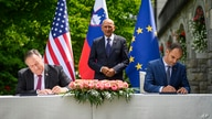U.S. Secretary of State Mike Pompeo, left, and Slovenia's Foreign Minister Anze Logar sign an agreement on fifth-generation internet technology as Slovenia's Prime Minister Janez Jansa stands at center, in Bled, Aug. 13, 2020.