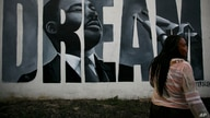 Lorinda Lacy, 45, stands outside her party store painted with a mural depicting Martin Luther King Jr., in the Watts neighborhood of Los Angeles, June 30, 2020.