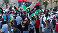 Demonstrators march during an anti-government protest in Tripoli, Libya, Aug. 25, 2020.