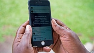 A woman reads a message on social media tax as she scrolls through her Facebook account on her phone in Kampala on July 5, 2018…