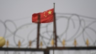 This photo taken on June 4, 2019 shows the Chinese flag behind razor wire at a housing compound in Yangisar, south of Kashgar,…