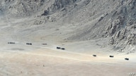 Indian soldiers walk at the foothills of a mountain range near Leh, the joint capital of the union territory of Ladakh, on June…