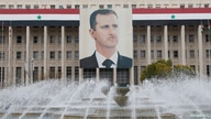 The picture of the Syria's President Bashar al-Assad is seen on central bank building in Damascus February 24, 2012. REUTERS…