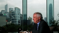 FILE - Former Hong Kong Governor Chris Patten sits in a hotel restaurant overlooking Hong Kong's financial Central district during an interview by Reuters in Hong Kong, March 15, 2012.