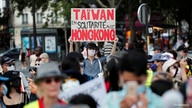 "A man wearing a protective mask holds a placard reading: ""Taiwan in solidarity with Hong Kong"" as people demonstrate in support…"