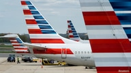 FILE PHOTO: A member of a ground crew walks past American Airlines planes parked at the gate during the coronavirus disease …