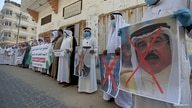 Palestinians hold crossed out posters depicting Bahrain's King Hamad bin Isa Al Khalifa, U.S. President Donald Trump and…