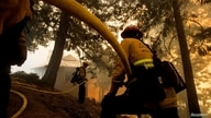 Firefighters battle a wildfire near a structure while defending the Mount Wilson observatory during the Bobcat Fire in Los…
